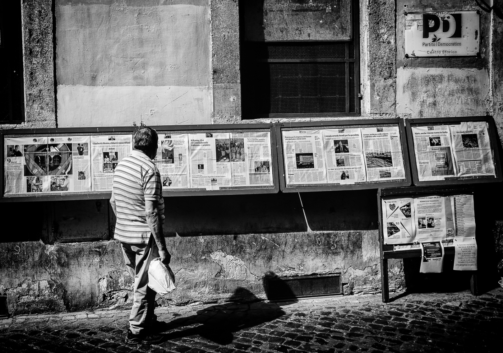 A man contemplating the newspaper outside the PD offices in Via dei Giubbonari